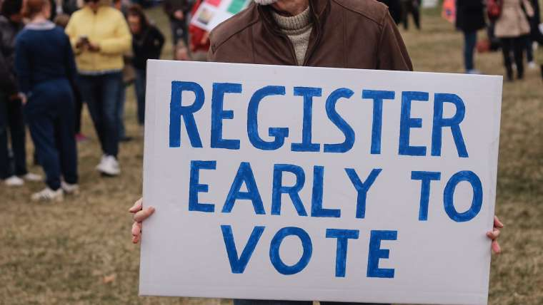 "Sign that reads ""Register Early to Vote""."